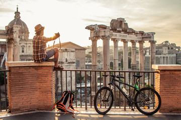 Young man tourist with backpack and bike sitting at Roman Forum at sunrise taking picture with vintage camera. Historical imperial Foro Romano from panoramic point of view, Italy