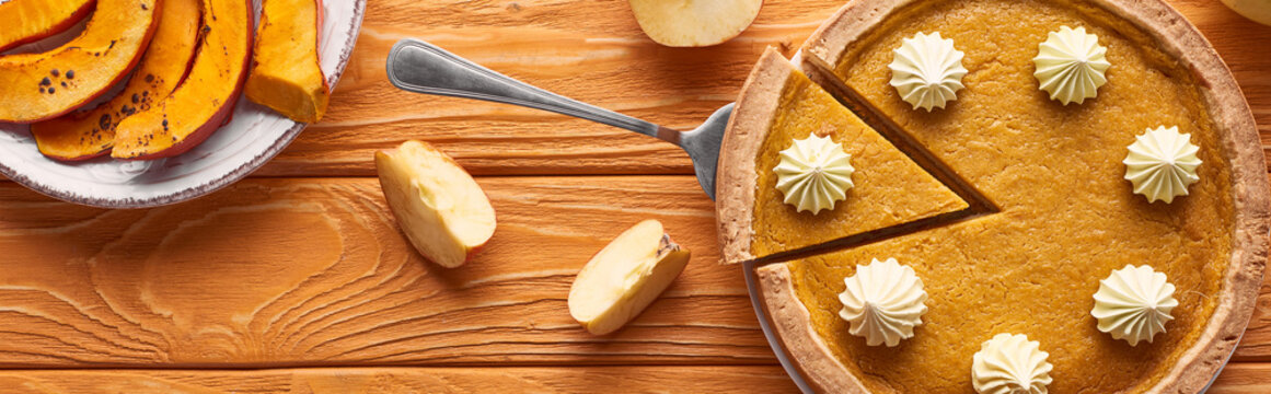 panoramic shot of tasty pumpkin pie with whipped cream near sliced baked pumpkin and cut apple on orange wooden table