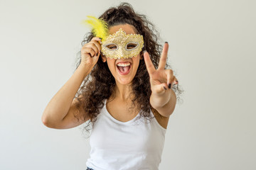 Deurstickers Carnaval Young woman smiling holding carnival mask on white background