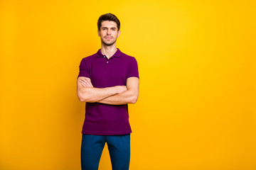Photo of white serious confident clever man standing with hands folded wearing trousers pants blue isolated over yellow vibrant color background