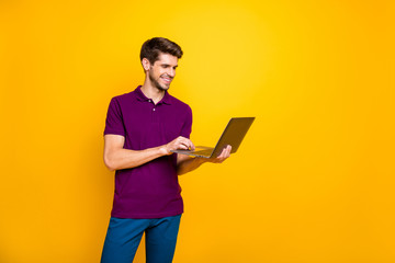 Portrait of his he nice attractive content cheerful cheery guy using laptop working online isolated over bright vivid shine vibrant yellow color background