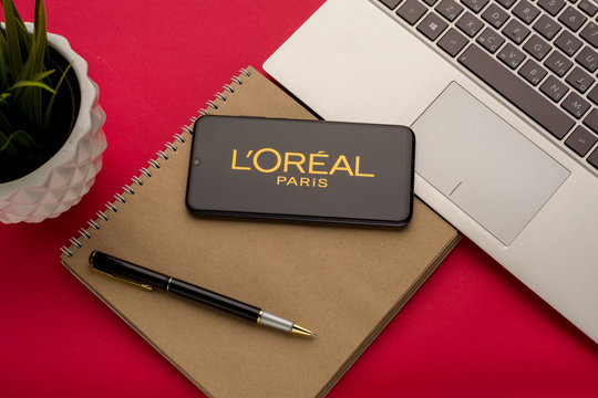 Tula, Russia - october 19, 2019: LOreal Group displayed on a smartphone near modern laptop on red background
