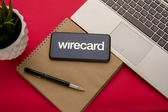 Tula, Russia - october 19, 2019: Wirecard displayed on a smartphone near modern laptop on red background