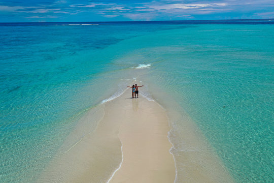 Romantic couple on beautiful white sandy beach on sandbank surrounded by turquoise water from aerial view