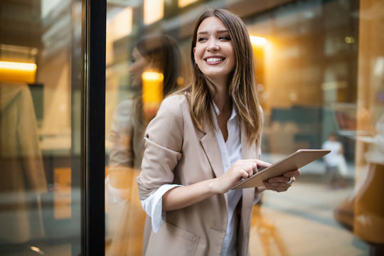 Urban happy business woman using tablet computer and working
