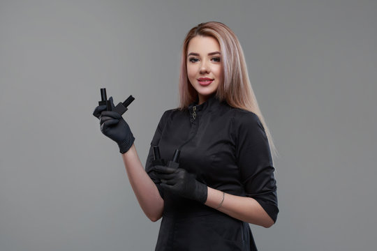 Portrait of a cute blonde girl manicurist holding in her hands gloved bottles with nail polishes isolated on a gray background.