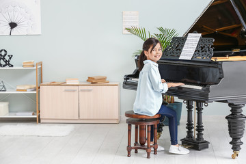 Little girl playing grand piano at home