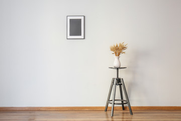 Table with wheat spikelets in vase and photo frame on white wall in room
