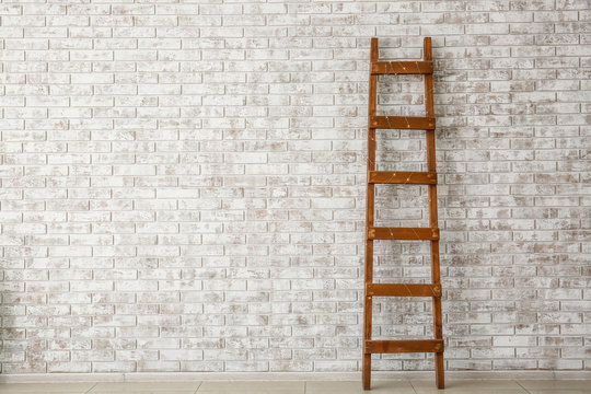 Wooden ladder near brick wall