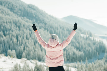 Happy woman in jacket standing and raising hands up in snowy mountain scenery. Bac view.