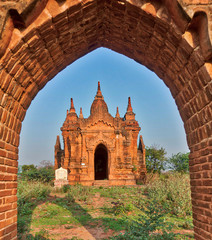 Simple ancient brick temple of Bagan Myanmar framed by brick entrance