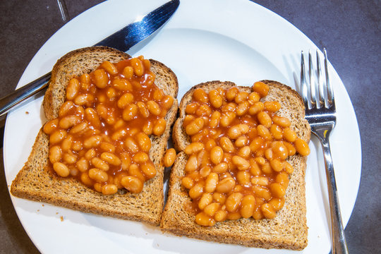 Baked beans on toast. Baked beans on two slices of brown whole meal toast. Toast topped with British baked beans. Simple breakfast meal. White plate with knife and fork.