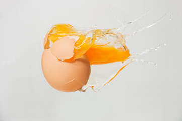 cracked egg with yolk on white background