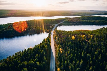 Foto auf Leinwand Wasserfalle Aerial view of bridge across blue lakes with sun light in colorful autumn forest in Finland.