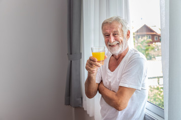 Senior elderly man standing at window in bedroom after waking up in morning with juice, looking camera