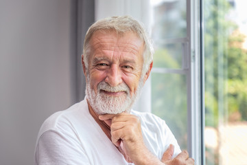 Senior elderly man standing at window in bedroom after waking up in morning, looking camera