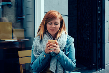 a young redhead woman sitting outside smiling and holding on her hands a cup of a tasty creamy coffee