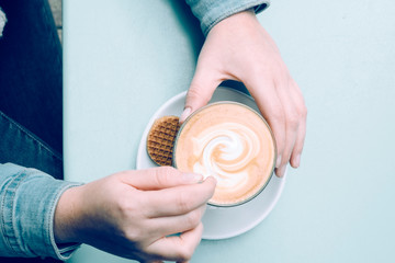 high angle view and close up of female hands holding a cup of coffee and mixing with a teaspoon the foam