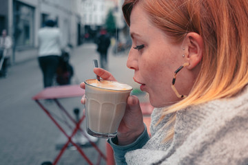 close up portrait of a young woman sitting outdoors in an urban environment relaxing and drinking a creamy coffee in the autumn season