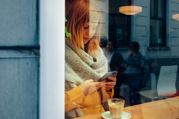 young woman sitting at a bar window in city street holding a mobile phone in her hands while drinking coffee
