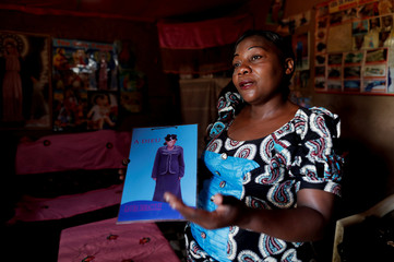 Ebola survivor and caregiver Arlette Kavugho holds a picture of her daughter who died of Ebola at her home in the eastern Congolese town of Butembo