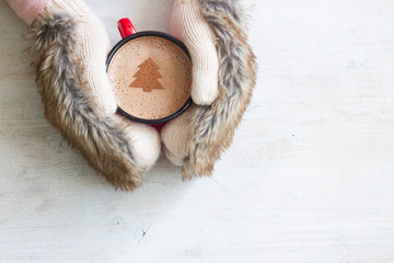 Hands in fur gloves holding mug of hot cocoa on a white wooden background