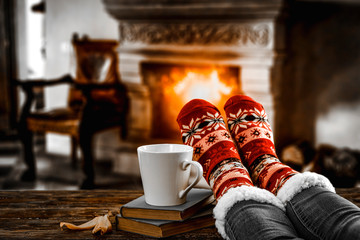 Wall Mural - Legs in winter christmas socks on wooden top board with fireplace background in cozy home interior.
