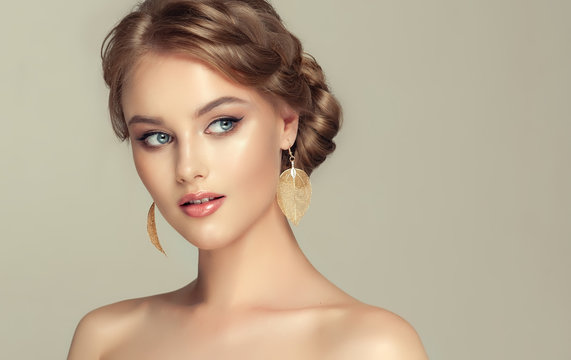 Beautiful model girl with elegant hairstyle and fashionable leaflet earrings . Woman with fashion  hair   and  accessories and jewelry ..