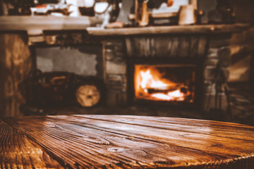 Fototapete - Wooden top with cosy warm home interior with fireplace background.