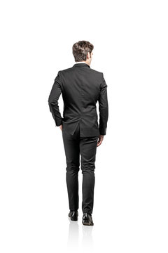 Rear view of walking businessman, isolated