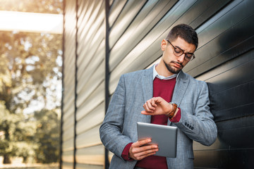 Businessman using digital tablet outdoors - Stock Image