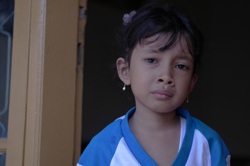 Little Asian girl showed sad expression. Cute Indonesian kid.