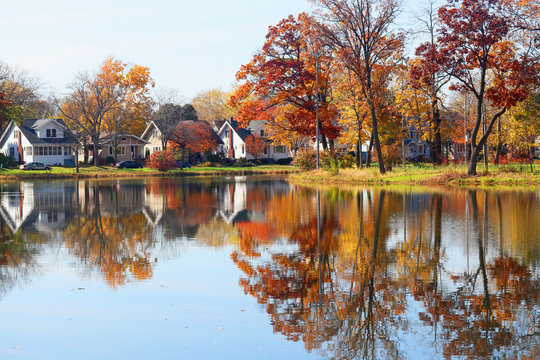 Beautiful autumn Midwest nature background.Fall view of private houses neighborhood with classic American middle class homes and colorful trees along a pond reflected in a water.Tenney Park,Madison,WI