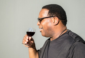 profile of a middle aged African American man about to sip from a glass of red wine against a solid background with copy space