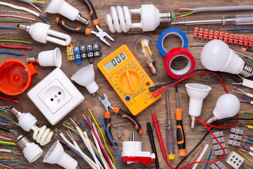 Electrician equipment on wooden background,  top view
