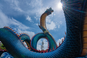 Giant Thai Naga Statue with blue sky clouds in the Phu Manorom Temple, Statue of Naka Buddha and White large Buddha statue at Mukdahan Province, Thailand.