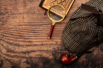 Fototapeta Literary fiction, investigate crime and mystery story conceptual idea with sherlock holmes detective hat, smoking pipe, retro magnifying glass and old book isolated on wood table top with copy space obraz
