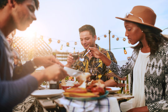 Group of diverse friends having dinner al fresco in urban settin