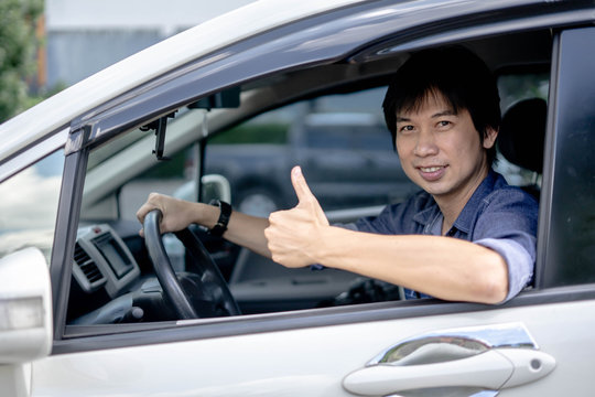 Happy asian man sitting in his van with thumbs up.