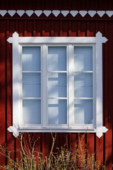 Traditional white framed window in red scandinvavian wooden house, seen in Lahti / Finland