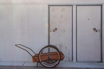 Cart for transportation to be used with a bicycle is parked outside a building with two doors