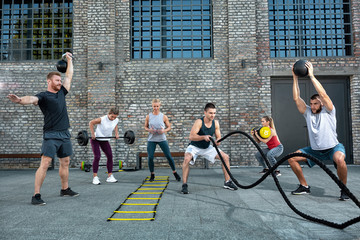 Group of healthy people working out, outside workout Wall mural