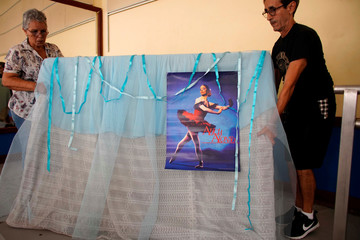 Workers carry an image of late Alicia Alonso, Cuban prima ballerina assoluta and founder of the Cuban National Ballet, at the National Ballet School in Havana