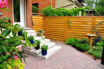 Contemporary with traditional elements, this beautiful small urban backyard garden features a red brick paver herringbone pattern patio, and extra wide natural stone steps.