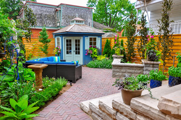 Contemporary with traditional elements, this beautiful small urban backyard garden features a seat wall, red brick paver herringbone patio, high end shed,  and mixed planting for colour and privacy.