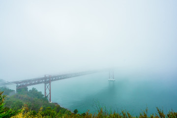 View on Fog at the Ponte 25 de Abril is a suspension bridge across the river Tejo, Portugal