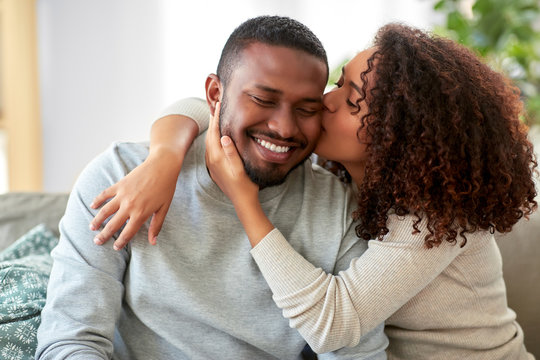 love, valentines day and relationships concept - happy african american couple sitting on sofa at home and kissing