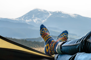 Women's legs in blue jeans and fun socks with a bright yellow pattern lie on the edge of the yellow tent. Mountain ranges covered with green forest and snow. View from the open tent.