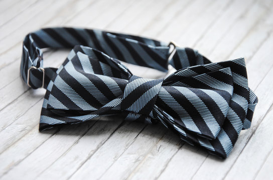 Striped blue bowtie on a wooden background. Accessory for formal dress. Symbol of elegance and fashion for men. Men's casual. Men's and women's accessories. Men's and women's bow tie.