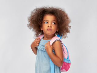 childhood, school and education concept - sad little african american girl with backpack over grey background
